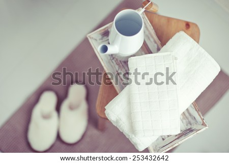 A pair of slippers on the carpet for a bathroom with a towel on a chair. - stock photo