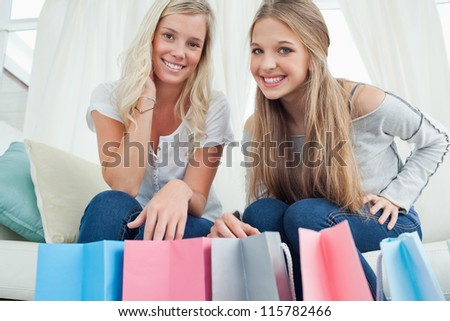 A pair of smiling girls with bags by their feet as the look at the camera - stock photo