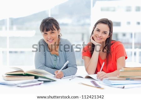 A pair of smiling students studying together as they look at the camera - stock photo