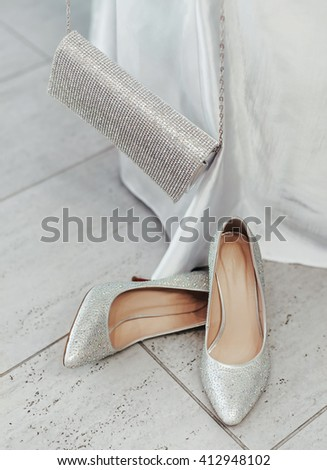 a pair of sparkling silver shoes on the floor and a matching purse - stock photo