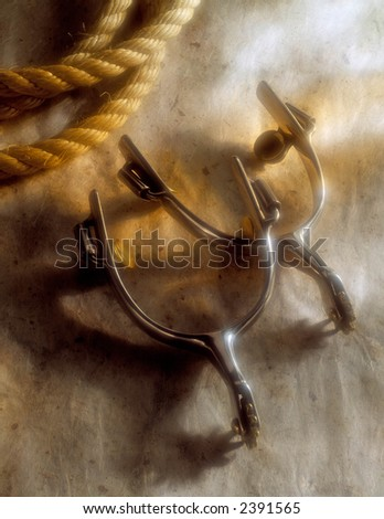 A pair of Spurs and a rope with warm lighting - stock photo