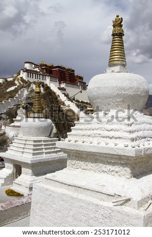 A pair of stupas in front overlook the Potala Palace, the residence of the exiled Dalai Lama in Lhasa, the capital of Tibet. - stock photo