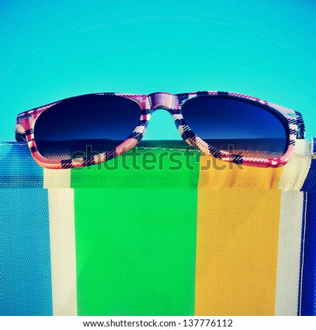 a pair of sunglasses on a colorful deckchair on the beach - stock photo