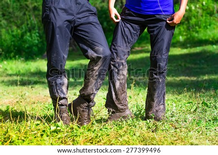 a pair of tourists after overcoming difficult obstacles on the mountain areas of the dirt road. Pants, boots in the mud.