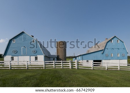 A pair of unusual blue barns in rural Maryland - stock photo