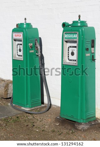 A pair of vintage Gas/Petrol pumps near an old garage. - stock photo