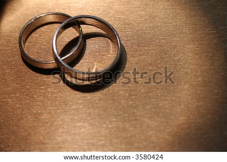 A pair of wedding bands against a gold-colored background. - stock photo