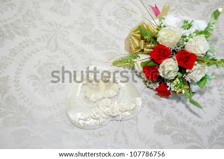 a pair of wedding rings and bridal bouquet of flowers on the bed - stock photo