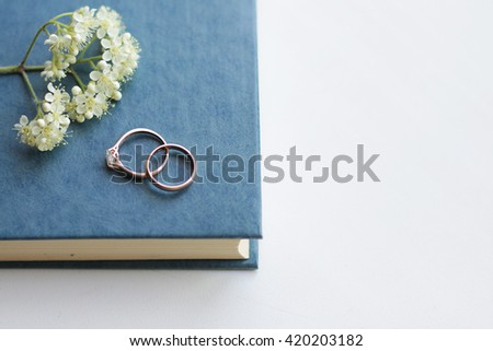 a pair of wedding rings on a book - stock photo