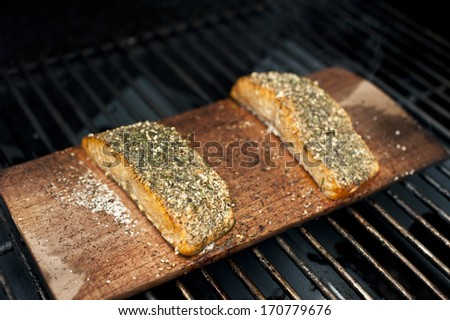 A pair of well seasoned wild Alaskan salmon fillets on a cedar plank being grilled. - stock photo
