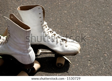 A pair of well used, adjacent roller skates awaits the next skater to exercise. - stock photo