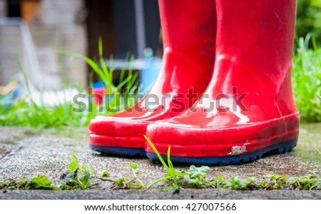 A pair of wet red children's wellies outside in a garden in the rain - stock photo