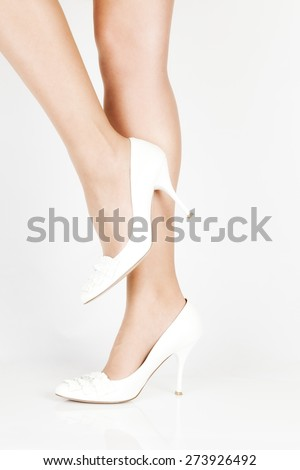a pair of white shoes with beautiful legs on a white background. close-up - stock photo