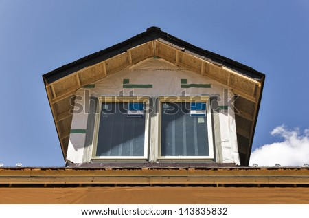 A pair of windows have just been installed in a rooftop dormer window of a new building under construction. There is room for copy space in the sky. - stock photo