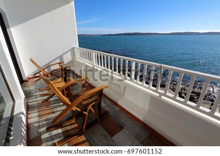 a pair of wooden rocking chairs sit on a deck or balcony of a house overlooking