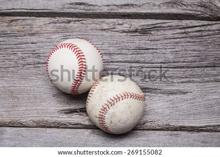 A pair of worn baseballs sit on a rustic wooden background. - stock photo
