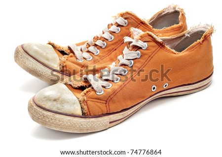 a pair of worn sneakers on a white background - stock photo