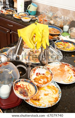 A pair of yellow dish washing gloves hangs on a sink faucet surrounded by filthy dishes. - stock photo