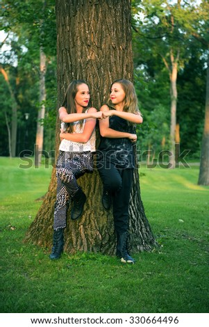 A Pair of Young Teenage Best Friend Girls give a fist pump in an outdoor park setting - stock photo