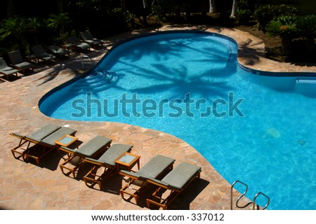 A palm tree's shadow is cast  on the water of a swimming pool at a resort hotel on the Big Island of Hawaii. - stock photo