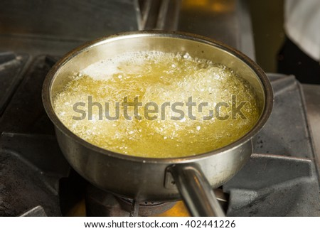 A pan of hot bubbling boiling oil in a silver pan on a hob. - stock photo