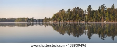 A panorama of a typical northern Minnesota lakeshore on a calm morning during Spring - stock photo
