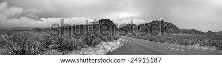a panorama of the cloud enshrouded Chisos Mountains in Big Bend National Park - stock photo