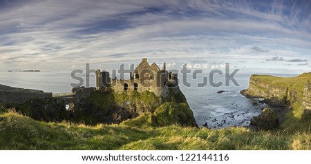 A panorama of the famous Dunluce Castle - a great tourist attraction from County Antrim, Northern Ireland. - stock photo