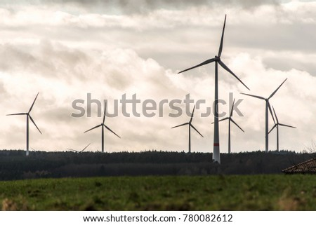 A panorama view over wind farm landscape in Germany with white generator turbines