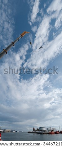 A panoramic image of an action sports thrill seeker after jumping from a bungee platform. - stock photo