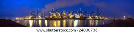 A panoramic image of  three container ships being unloaded at night at a busy commercial harbor, with a small trawler moored alongside. - stock photo