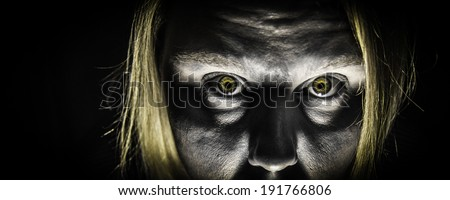 A panoramic photo of a zombie with bright yellow zombie eyes - stock photo