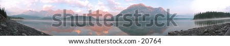 A panoramic shot of a lake with trace amounts of fog in the rocky mountains. - stock photo