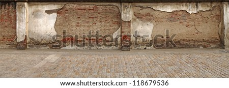 A panoramic stretch of damaged grungy red clay brick wall along a cobble stone sidewalk. - stock photo