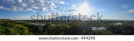 A panoramic view looking East from the west bluff of the Rio Grande River at the Sandia mountains in Albuquerque, New Mexico. - stock photo