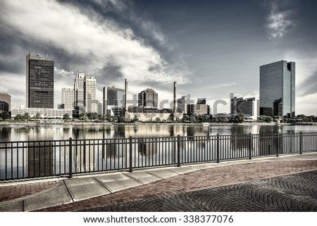 A panoramic view of downtown Toledo Ohio's skyline from across the Maumee river at a popular restaurant area with a paver brick boardwalk and a decorative iron railing..