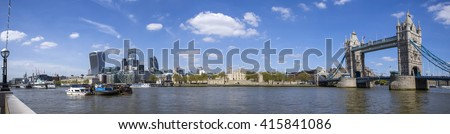 A panoramic view of London taking in the sights of Tower Bridge, the River Thames, Tower of London, the skyscrapers in the City of London and the HMS Belfast. - stock photo