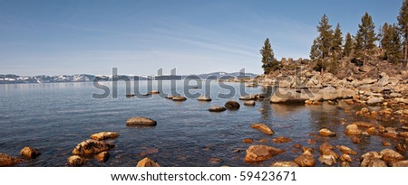 A panoramic view of the California side of Lake Tahoe from the rocky Nevada shoreline.