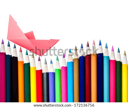 A paper boat floating on a row of color pencils isolated on white with copy space - stock photo