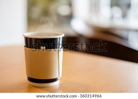 A paper cup containing a hot coffee on wooden table in cafe with blur background.