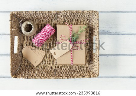 A paper parcel with a pine branch, wrapped tied with a tag on a tray. Christmas gift box wrapped with paper kraft and tied with red & white baker's twine on a white wooden table. Vintage Style. - stock photo