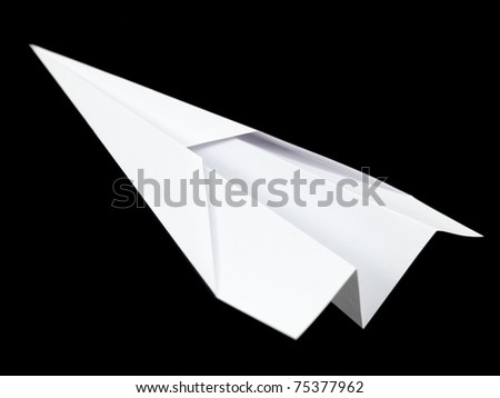 A paper plane isolated against a black background - stock photo