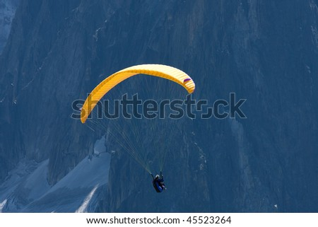 A para-glider flies  in front of a high mountain - stock photo