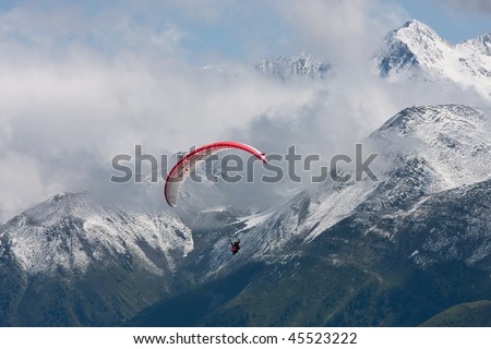 A para-glider flies over snow covered mountains in the swiss alps - stock photo