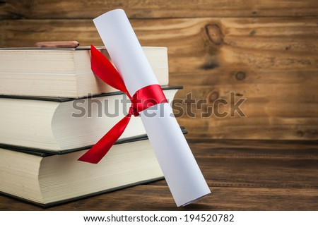A parchment diploma scroll, rolled up with red ribbon beside a stack of books on wood background - stock photo