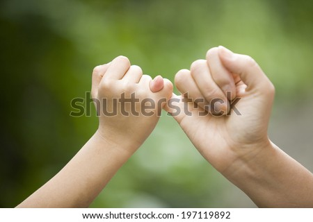 A Parent And The Child Hooking Their Fingers To Make A Promise