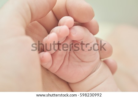 A parent holding the hand of a newborn baby