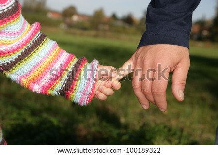 A parent holding the hand of its child while walking in a park............ - stock photo