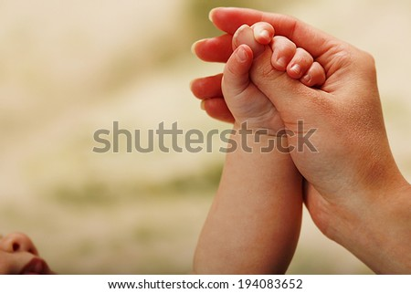 a parent holds the hand of a small child - stock photo
