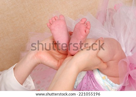 A parents hands tenderly hold their newborns feet - stock photo